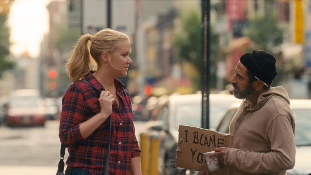 Amy (AMY SCHUMER) charla con Noam (DAVE ATTELL), el sintecho del barrio, en Y DE REPENTE TÚ