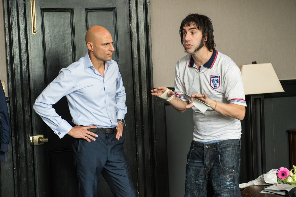 Nobby (Sacha Baron Cohen) surprises Sebastian (Mark Strong) at his London flat in Columbia Pictures' THE BROTHERS GRIMSBY.